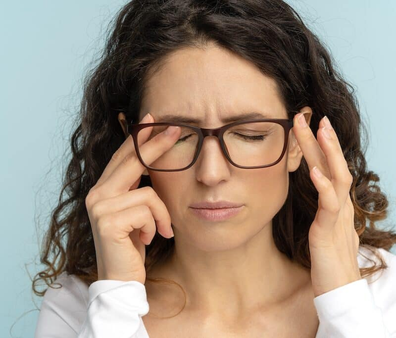Allergy woman in glasses rubbing eyes suff